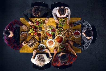 Photo for Top view creative photo of friends sitting at wooden vintage table. Friends of six having dinner. They with plates full of delicious meal and glasses with drinks - Royalty Free Image
