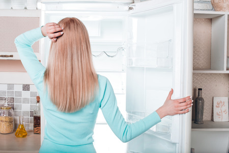 Photo pour What's for dinner? Pretty blonde standing near open empty fridge. Back view photo of thoughtful young woman. She looking at fridge - image libre de droit