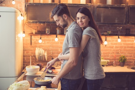 Photo pour Young couple cooking in kitchen - image libre de droit
