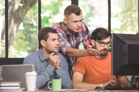Foto de Young men programmers working together in the office - Imagen libre de derechos