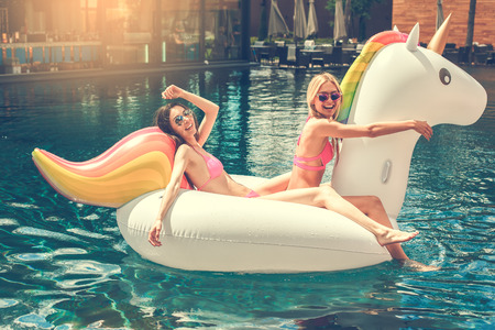 Photo pour Young women friends in the swimming pool fun - image libre de droit