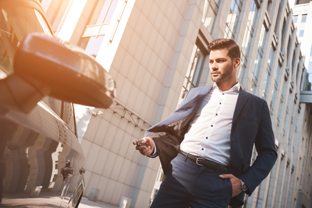Photo pour This car is perfect for me. Cheerful mature man in formalwear looking at camera and smiling while standing near his new car - image libre de droit