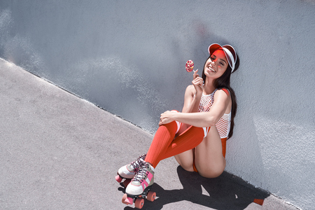 Photo for Happy beautiful young woman riding on rollers, eating candy. Summer photo. - Royalty Free Image