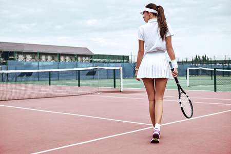 Photo for Enjoying the game! Rear view legs of a sexy sporty woman on tennis court. Beautiful female tennis player with tennis racket and balls in the sport club. Sports Fashion. - Royalty Free Image