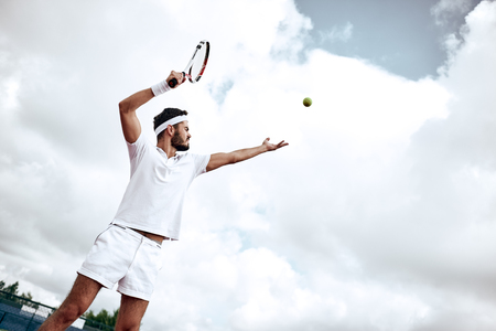 Foto de Professional tennis player playing a game of tennis on a court. He is about to hit the ball with the racket. The ball is suspended in the air. - Imagen libre de derechos