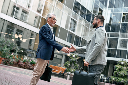 Photo for Meeting is started. Young and senior smiling businessmen shaking hands together while standing outdoors on the city background - Royalty Free Image