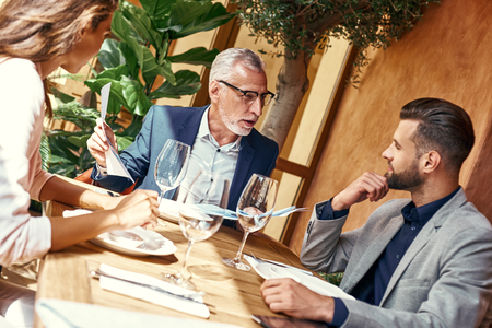 Photo for Business lunch. Three people in the restaurant sitting at table negotiating about contract. Team work concept - Royalty Free Image