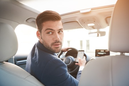 Photo for Portrait of stylish confident businessman in car wearing black suit, turning to back seats with serious expression. - Royalty Free Image