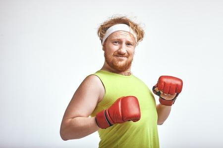 Foto de Red haired, bearded, plump man wearing sportswear and red boxing gloves - Imagen libre de derechos