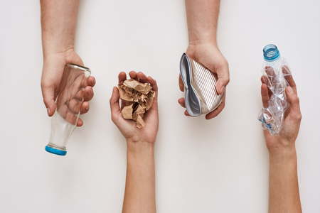 Foto de Sparate your trash. Four types of garbage in human hands - Imagen libre de derechos