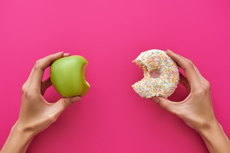 Photo for Dieting or good health concept. Young woman trying to choose between apple and donut - Royalty Free Image
