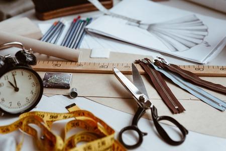 Foto de Tailors tools, scissors, measure tape and ruler on the sartorial work table - Imagen libre de derechos
