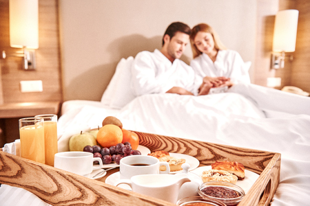 Photo pour Food in a bed. Couple are hugging in hotel room bed - image libre de droit