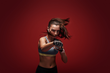 Photo pour Hustle to gain more muscle. Sportswoman standing concentrated in gym gloves over red background. - image libre de droit