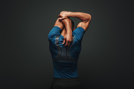 Foto de Even if you dont have time for a big workout, stretching in the morning and night really changes your body. Sportsman is stretching standing over dark background - Imagen libre de derechos