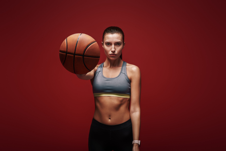 Photo pour Take care of your body. Sportswoman with ball standing over red background - image libre de droit