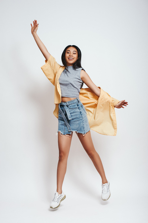 Photo for Flying away. Lovely young asian woman in casual wear looking at camera and smiling while jumping against grey background - Royalty Free Image