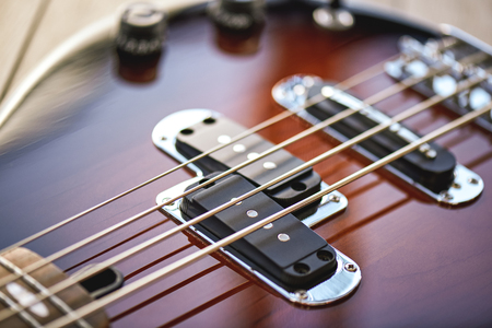 Photo for Guitar Lessons. Close-up view of electric guitar body with metal strings, volume and tone controls - Royalty Free Image