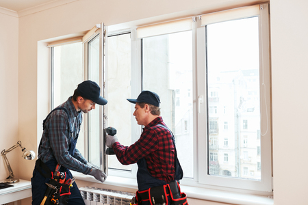 Photo pour Quality light. Construction workers installing new window in house together - image libre de droit