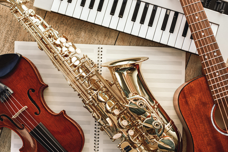 Foto de Power of music. Top view of musical instruments set: synthesizer, guitar, saxophone and violin lying on the sheets for music notes over wooden floor - Imagen libre de derechos