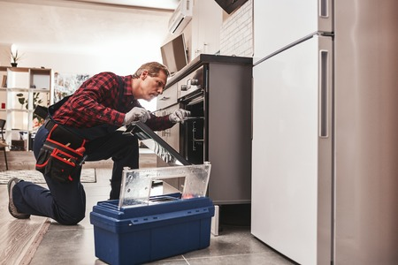 Photo pour Whats up with oven. Full length of repairman examining oven - image libre de droit