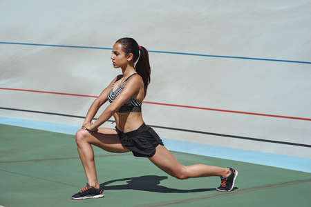 Photo for More stretching, less stressing. Attractive athlete on the stadium track. Woman summer fitness workout. Jogging, sport, healthy active lifestyle concept - Royalty Free Image
