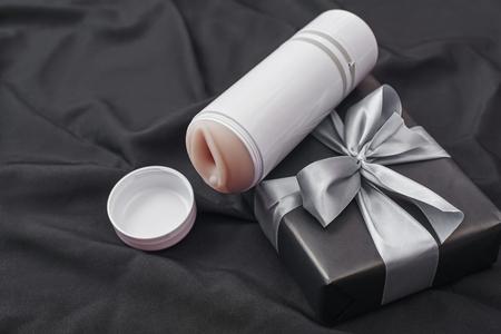 Foto de Sex toy gift for man you love! Close-up photo of male masturbator and gift box arranged on a black silk fabric - Imagen libre de derechos
