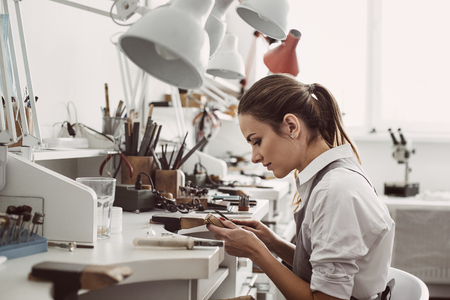 Foto de Working all day. Side view of young female jeweler sitting at her jewelry workshop and holding in hands jewelry tools for making accessories - Imagen libre de derechos