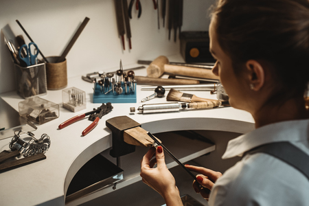 Foto de Focused on a process. Back view of a female jeweler working and shaping an unfinished ring with a tool at workbench in workshop. - Imagen libre de derechos