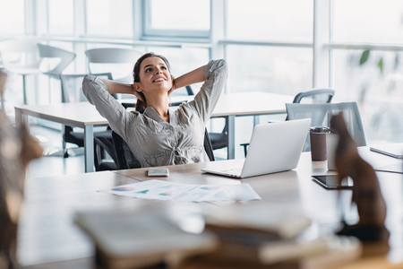 Photo for Happy businesswoman relaxing with hands behind head at office desk. Daydreaming concept - Royalty Free Image