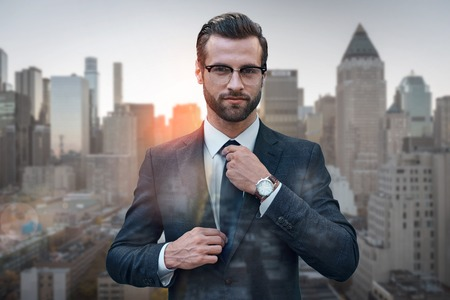 Photo for Perfect style. Confident business expert in glasses adjusting necktie while standing against of morning cityscape background. Fashion look. Business style. Success concept - Royalty Free Image
