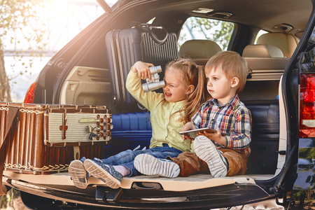 Photo pour Little cute kids having fun in the trunk of a car with suitcases. Family road trip - image libre de droit