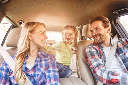 Foto de To travel is to live. Smiling family sitting in the car and driving. Family road trip - Imagen libre de derechos