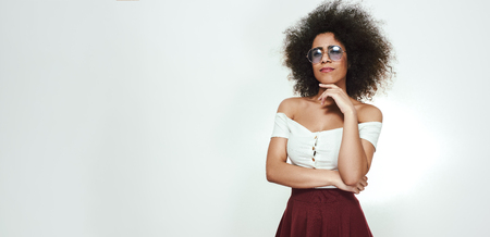 Photo for Wide photo of attractive afro american woman in stylish eyewear and sexy clothes touching her chin with hand and thinking. Web Banner - Royalty Free Image