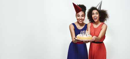 Photo for Time to make a wish! Wide photo of happy young afro american women in party hats holding a cake with candles while celebrating birthday - Royalty Free Image