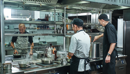 Photo for Cooking process. Professional team of chef and two young assistant preparing food in a restaurant kitchen - Royalty Free Image