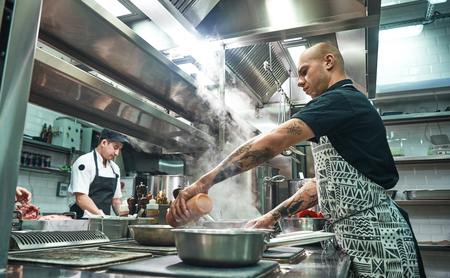 Photo for How to cook a meat Concentrated young chef in apron and cooks preparing food together in a restaurant kitchen - Royalty Free Image
