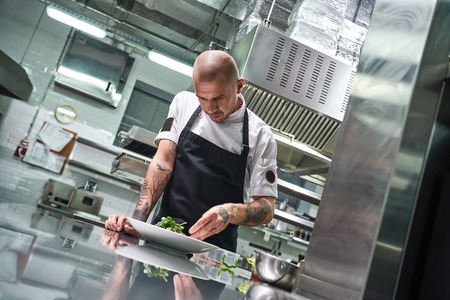 Photo for Food concept. Portrait of handsome professional chef in black apron decorating a salad on the plate while working in restaurant kitchen - Royalty Free Image