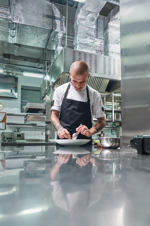 Photo for Working in a restaurant. Vertical portrait of professional male chef with tattoos on his arms garnishing his dish on the white plate - Royalty Free Image