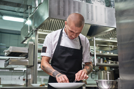 Photo for Finishing a dish. Attractive male chef with beautiful tattoos on his arms garnishing his dish on the plate in restaurant kitchen - Royalty Free Image