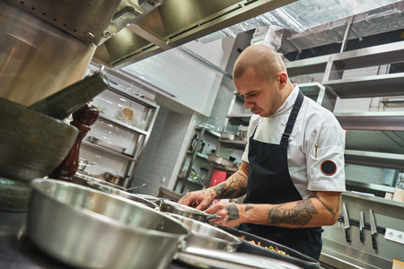 Photo for Inspiration in cooking. Young male chef with several tattoos on his arms is garnishing italian pasta in a restaurant kitchen. - Royalty Free Image