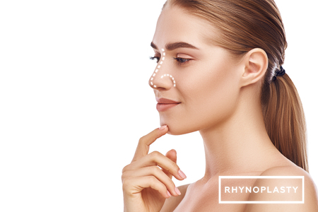 Photo pour Rhinoplasty - nose surgery. Side view of attractive young woman with perfect skin and dotted lines on her nose isolated on white background. Plastic surgery concept - image libre de droit