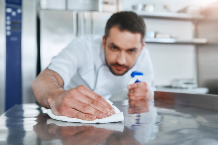 Photo for Hygienic precautions. Worker in restaurant kitchen cleaning down after service. Selective focus on his hand - Royalty Free Image