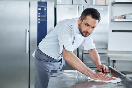 Photo for When preparing foods keep it clean, a dirty area should not be seen. Young male professional cook cleaning in commercial kitchen - Royalty Free Image