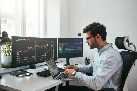 Foto für Workplace of trader. Young bearded trader wearing eyeglasses using his laptop while sitting in office in front of computer screens with trading charts and financial data. Stock exchange. Financial trading concept. Investment concept - Lizenzfreies Bild