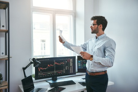 Foto de Trading strategy. Smart and young trader in eyeglasses looking at financial reports and analyzing trading charts while standing in front of computer screens in modern office. Stock broker. Forex market. Trade concept - Imagen libre de derechos