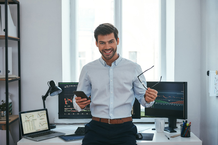 Foto de Great! Happy young businessman or trader in formalwear holding eyeglasses and smartphone and smiling while standing in front of computer screens with trading charts in the office. Forex market. Business concept. Investment concept - Imagen libre de derechos