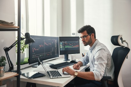 Photo pour Busy working day. Young bearded trader in eyeglasses working with laptop while sitting in his modern office in front of computer screens with trading charts. - image libre de droit