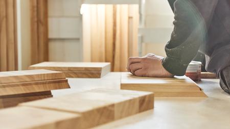 Photo pour Carpenter working with wooden pieces in carpentry shop. Horizontal shot - image libre de droit
