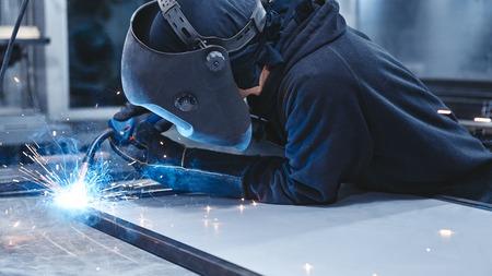 Foto de Male worker wearing helmet and gloves welding steel construction at the factory. Horizontal shot. Close up. Side view - Imagen libre de derechos